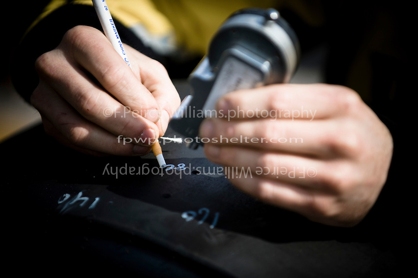 A crewmember on the car of Brian Scott (#11) checks race used tires for tread depth.