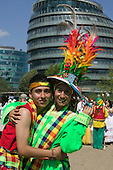Carnaval del Pueblo carnival celebrations in London. South American nationals assemble for a parade in costumes. London's City Hall is in the background.