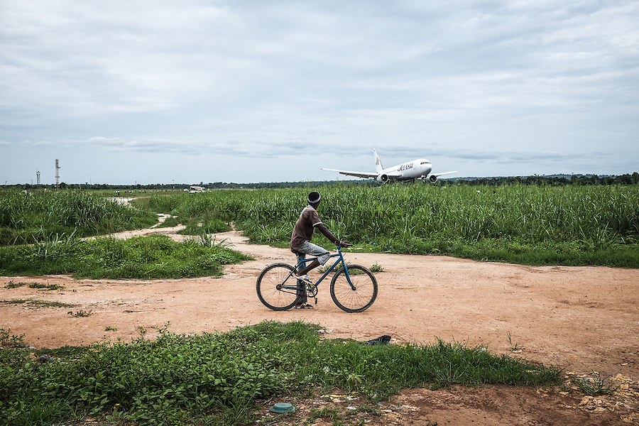 CAR, Bangui: Zone of the Mpoko camp next to the runway of the Mpoko airport. In order to reach the other part of the camp on the other side of the runway, people have to wait that the plane passes before crossing.  17th April 2016.<br /> RCA, Bangui : Zone du camp Mpoko &agrave; c&ocirc;t&eacute; de la piste de l'a&eacute;roport Mpoko . Afin d' atteindre l'autre partie du camp de l'autre c&ocirc;t&eacute; de la piste , les gens doivent attendre que l'avion passe avant de traverser . 17 avril 2016.