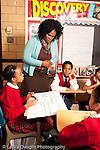 K-8 Parochial School Bronx New York Grade 5 social studies students working in small groups female teacher checking in with group vertical