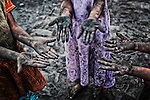 Three young girls out to collect the left-over and thrown-way pieces of coal from the Steam Engine of the Indian Railways, show their working hands. They collect these pieces of coal for the family to cook their evening meals. Photography : © Santosh Verma