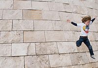 Felix and Lucas jumping from a wall at the Getty Museum, Los Angeles, California.