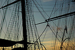 Masts and rigging of Cutty Sark ship silhouetted against sunset Greenwich London England
