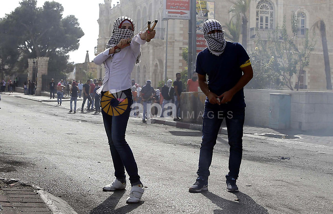 A female Palestinian protester uses a sling shot to throw stones at Israeli security forces during clashes in the West Bank city of Bethlehem, on October 13, 2015. A wave of stabbings that hit Israel, Jerusalem and the West Bank this month along with violent protests in annexed east Jerusalem and the occupied West Bank, has led to warnings that a full-scale Palestinian uprising, or third intifada, could erupt. The unrest has also spread to the Gaza Strip, with clashes along the border in recent days leaving nine Palestinians dead from Israeli fire. Photo by Muhesen Amren