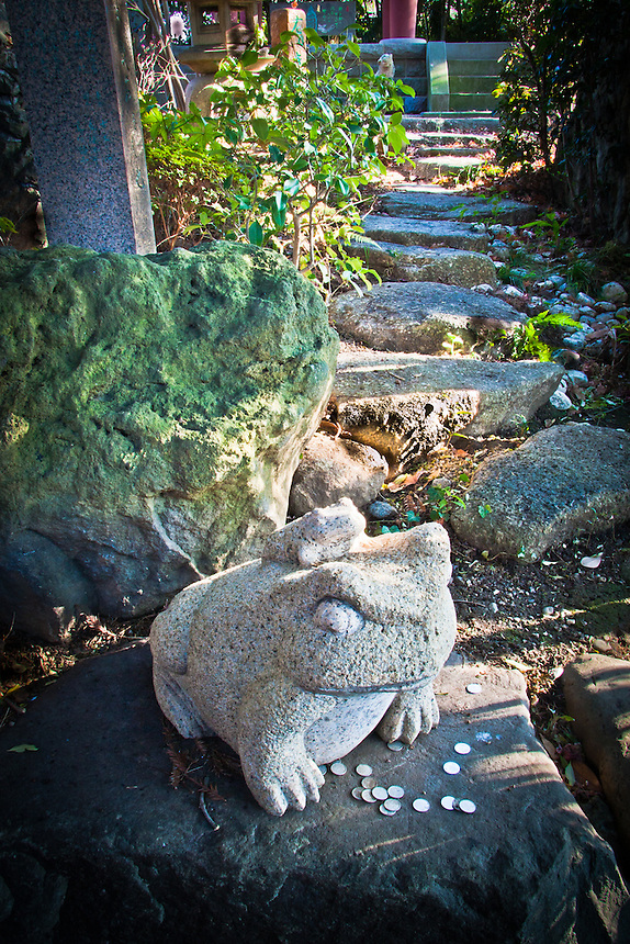 Stone frogs with coin offerings in Zenyomitsu-ji Buddhist temple Todoroki.