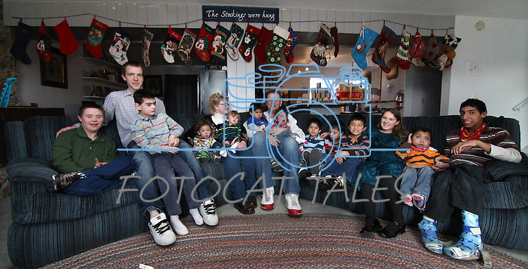 Merrill and Roberta Simon, center, have adopted 21 special needs foster kids over the years. The kids who currently live at home are, from left, Michah, 18, Jeremy, 20, Jericho, 13, McCoy, 2, Montana, 1, Maverick, 3, Macylea, 2, MacGyver, 5, Joey, 8, McClain, 9, Lisa Marie, 12, Joseph, 11, and Mordachi, 15. The Simons hang a Christmas stocking for all 23 members of the family, including some of the older kids who no longer live in the house..Photo by Cathleen Allison