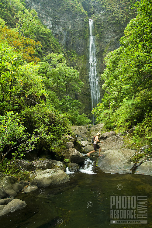 Young man hiking up to Hanakapiai Waterfall in Kauai's Na Pali coast