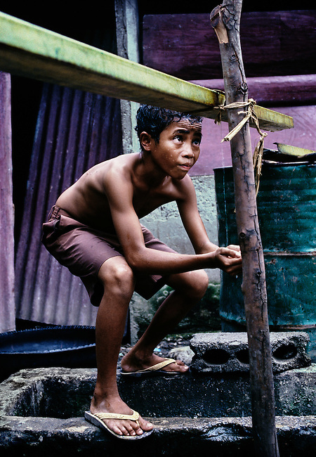 Young boy washing after taking refuge in a makeshift camp in Dili. <br />