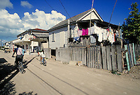 Native people ride bicycles in the streets of San Pedro on the island of Ambergris Caye, Belize. Natives riding bicycles. San Pedro Ambergris Caye Belize Central America.