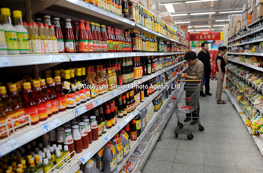 Chinese customers buying sauce at a Wu Mart supermarket in Beijing, China.  Wu Mart, the Beijing-based chain, was founded in the early 1990s by Zhang Wenzhong. Its name smacks of the fame of U.S. retail giant Wal-Mart. Wu Mart and Wal-Mart are competing in different arenas and each appears to be going after a different class of consumer. By 2005, Wu Mart had more than 450 hypermarkets, supermarkets and convenience stores, and is one of only a few Chinese retailers whose shares are publicly traded..28 May 2011