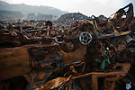 Burned out vehicles are among the masses of other waste piled up on the outskirts of Yamada, Iwate Prefecture, Japan on 10 June 2011. Authorities are unable to dispose of much of the debris created by the March disasters due to fears of radiation contamination, leading to giant mounds of waste that are becoming increasingly more toxic. The disaster is estimated to have left behind some 25 million tons of waste. Photograph: Robert Gilhooly
