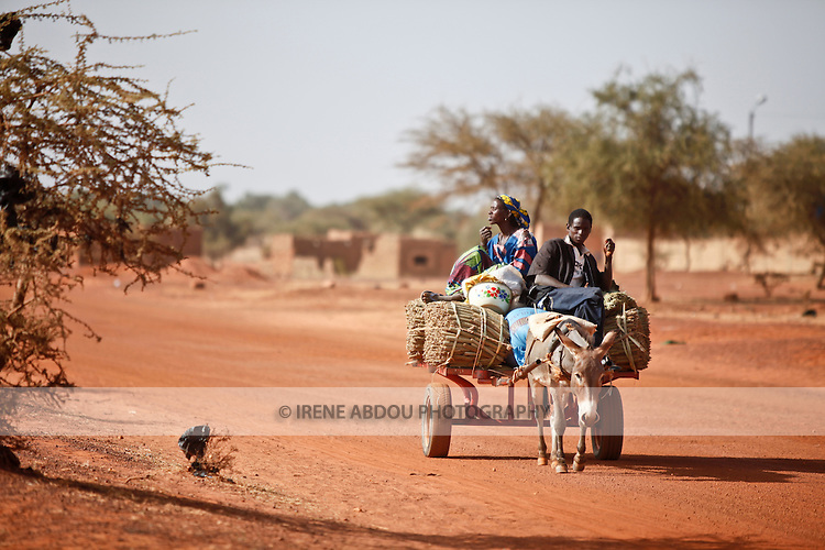"In West Africa, certain villages have markets that ""assemble"" at regular intervals, such as weekly or every three days.  People from villages around the region come to Djibo's weekly Wednesday market in northern Burkina Faso to buy and sell food, livestock, and other goods and services.  Here, a family brings harvested millet to market by donkey cart."