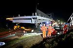 WEESP - In het holst van de nacht schuift transportspecialist Ale uit Breda, de door ingenieursbureau Movares ontworpen en door bouwcombinatie KWS-Mercon gebouwde stalen Weesperbrug, langzaam naar de landhoofden van de oude - en ondertussen verwijderde - Weesperbrug. De prefab in Gorinchem opgebouwde stalen boogbrug, is één van de vijf nieuwe bruggen die in opdracht van Rijkswaterstaat's project Kargo gebouwd worden, ter vervanging van verouderde bruggen en ter verhoging van de doorvaarthoogte voor vierlaagse containerschepen. De nieuwe brug is al geasfalteerd, en voorzien van leuningen, en straatlantaarns. COPYRIGHT TON BORSBOOM