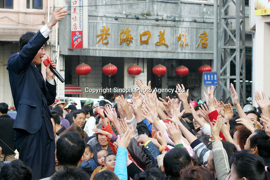 Audience eagerly grabs for free red packets on a street of Haikou city, Hainan Island, China. .14 Jan 2005