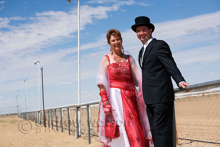 Race goers in costume dress for the fun of the Birdsville Races.  Every September the remote town of Birdsville comes alive with thousands of visitors for the Birdsville Cup, the most famous horse racing carnival in outback Australia.  Birdsville, Queensland, AUSTRALIA.