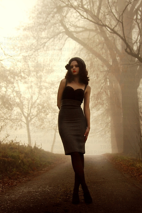 A vampy brunette in heels, a corset and a tight skirt posing in a foggy park.