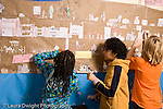Elementary school Grade 4 social studies project two boys and a girl working on model of life on ship in earlier era horizontal