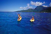 Kids and adult playing in kayaks in clear blue waters of Moorea lagoon, Moorea Island in background