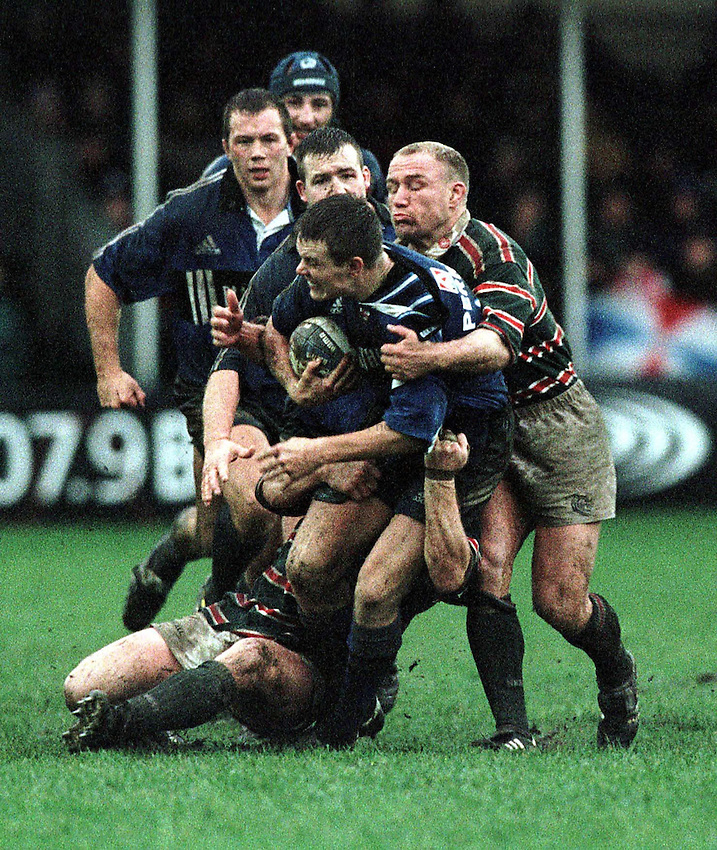 Photo. Richard Lane.Bath v Leicester. 26/12/99..Matt Perry is brought down by Neil Back as his forwards move in to support.