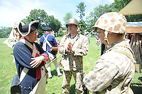 Tracey Fallon (L) of the Second Pennsylvania Regiment speaks with World War II reenactors Matt Naudasher (C) and Matt Davenport (R) during the Hatboro Tricentennial celebration at Pennypack Elementary School Saturday June 13, 2015 in Hatboro, Pennsylvania.  (Photo by William Thomas Cain/Cain Images)