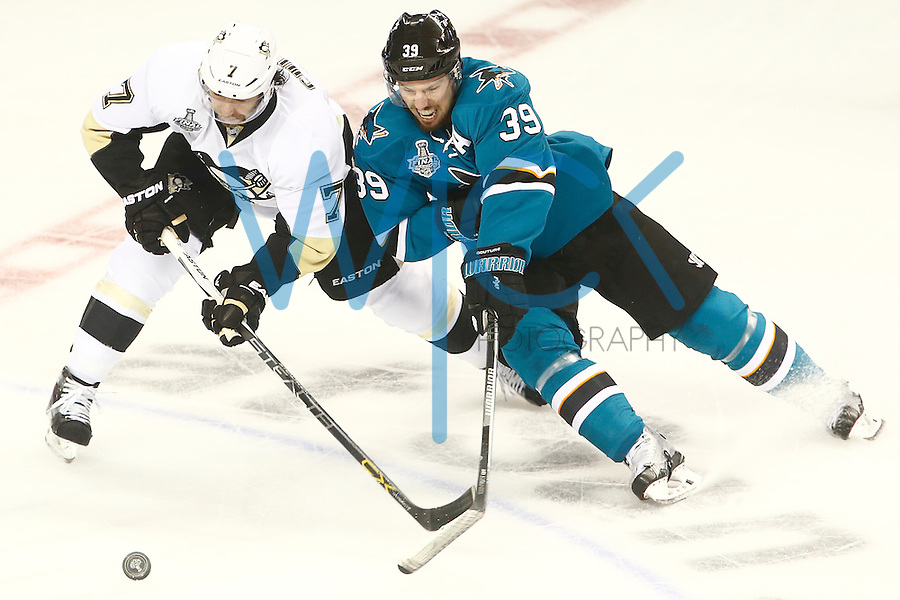 Matt Cullen #7 of the Pittsburgh Penguins and Logan Couture #39 of the San Jose Sharks reach for the loose puck in the first period during game four of the Stanley Cup Final at the SAP Center in San Jose, California on June 6, 2016. (Photo by Jared Wickerham / DKPS)