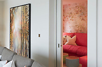 Behind the grey sofa in the main sitting room a set of sliding doors lead to a cosy children's television room in pink tones, which is furnished with painted tree trunk coffee tables and a comfortable sofa.