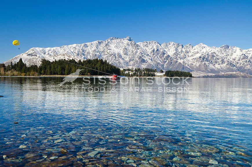 Para-sailing on Lake Wakatipu with snow covered Remarkables mountains behind, South Island, New Zealand.