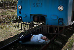 A man taking a nap in the shade of a locomotive on the railroad track.