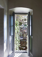 View from an open French window across the courtyard to a lush terrace and garden