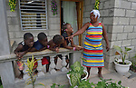 "Reseha Rosier talks with four of her grandchildren on the porch of her house in a model resettlement village constructed by the Lutheran World Federation in Gressier, Haiti. The settlement houses 150 families who were left homeless by the 2010 earthquake, and represents an intentional effort to ""build back better,"" creating a sustainable and democratic community. Four of Rosier's grandchildren, and their mother and father, live with the older woman."
