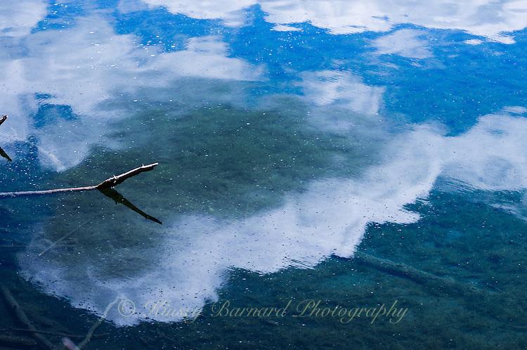White clouds and blue skies, reflecting on Surveyor Lake