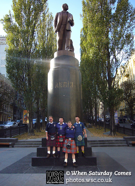Ukraine 2 Scotland 2, 11/10/2006. Olympic Stadium, Euro 2008 Qualifying. Scotland fans, members of the Tartan Army, pose for photographs under a statue of Communist leader Lenin the centre of Kiev prior to their team's match against Ukraine. Ukraine defeated Scotland 2-0 after a goal-less first half in this Euro 2008 group qualifying match played at the Olympic Stadium in Kyiv (Kiev). This was the first competitive international match between the countries. Photo by Colin McPherson.