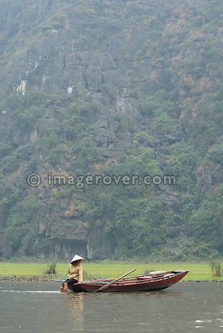 Asia, Vietnam, Tam Coc near Ninh Binh. In the watery landscape of Tam Coc (Three Caves) vietnamese woman working from her boat.
