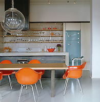 Orange furniture and accessories, such as the Eames DAX chairs and the crockery and glassware displayed on the open shelves, add colour to this contemporary kitchen