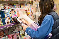 Woman reading gossip magazine at a news stand.