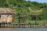 A man of the Anu-Parajuana ethnic group throws a fishing net in the Sinamaica Lagoon. Living much like their ancestors the Anu-Parajuana build simple houses on stilts. Fishing is their main source of income.