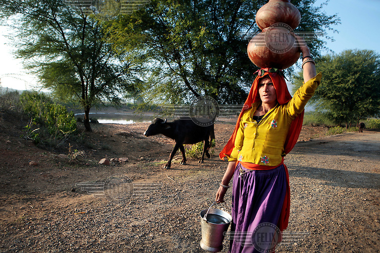 A woman carries vessels filled with water past a johad. This is a traditional rainwater harvesting structure consisting of an earth dam that collects water during the rainy season. Its water feeds a well while the pond also provides water for cattle...