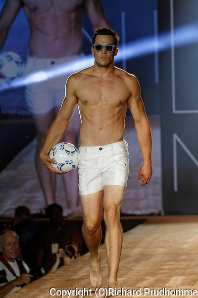 A male model wearing white shorts walks down the runway for the Nico fashion show held during the Fashion and Design Festival in Montreal