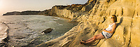 Panoramic photo of a tourist on Scala dei Turchi at sunset, Realmonte, Agrigento, Sicily, Italy, Europe. This is a panoramic photo of a tourist on Scala dei Turchi at sunset. Scala dei Turchi is a limestone cliff known as The Turkish Staircase on the Rossello cape at Realmonte near Agrigento in Sicily, Italy. It is without a doubt one of the best places I have ever watched the sunset, as the panoramic view of white limestone cliffs turn a rich orange.