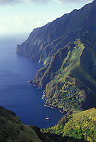 Yacht 'Heron' at anchor off mountain seacliffs of Hanavave, Fatu Hiva, Marquesas, French Polynesia