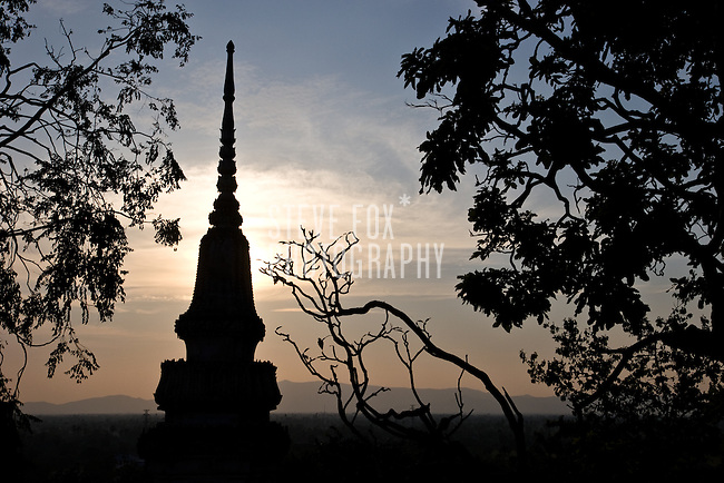 A sillhouette of a pagoda and tree branches with the mountains in the background as seen from Phra Nakhon Khiri Historical Park, Phetchaburi, Thailand