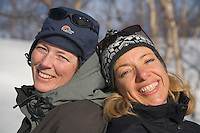 Sweden, SWE, Kiruna, 2006-Apr-16: Two women cheerfully sitting back to back in the snow.