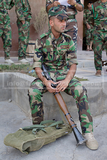 30/06/2014. Khanaqin, Iraq. A Kurdish peshmerga fighter sits with a rocket propelled grenade launcher at a Kurdish peshmerga base in Khanaqin, Iraq, as peshmerga prepare to head out and relieve troops at the front line in Jalawla. Counted by Kurds as part of their homeland, fighting in the town of Jalawla now consists of occasional skirmishes and exchanges of fire between snipers and heavy machine guns on both sides.<br /> <br /> The peshmerga, roughly translated as those who fight, is at present engaged in fighting ISIS all along the borders of the relatively safe semi-automatous province of Iraqi-Kurdistan. Though a well organised and experienced fighting force they are currently facing ISIS insurgents armed with superior armament taken from the Iraqi Army after they retreated on several fronts. &copy; Matt Cetti-Roberts