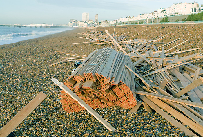 Wood washed ashore at Brighton after a container ship founders in rough seas.Britain is faces more severe flood warnings..[Beaches were closed along the Sussex coast last night [21 January 2008] as a massive clean-up operation began to remove thousands of pieces of timber washed ashore over the weekend..Worthing was hit hardest with 6ft piles of wood stacking up along the shoreline for as far as the eye could see..The drama began after 2,000 tonnes of timber fell overboard from the deck of the Greek-registered vessel Ice Prince before she sank in rough seas 26 miles off Portland Bill in Dorset on Tuesday..By Saturday morning beachcombers had descended on the 20ft and 33ft planks strewn across the shingle in Worthing..Birdwatchers scanning the channel with powerful telescopes warned there was a lot more timber out to sea..They had seen huge bundles of wood, lashed together, floating about a mile offshore.].[Thanks to Evening Argus for details].