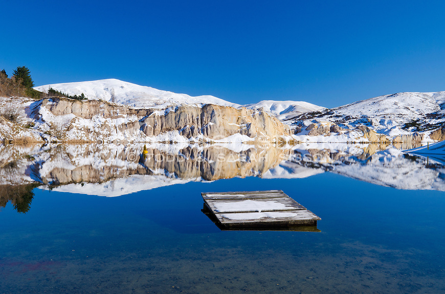 A perfect reflection of clay cliffs in the Blue Lake, St Bathans on a sunny blue sky day with pontoon on the lake. Central Otago, South Island, New Zealand - stock photo, canvas, fine art print