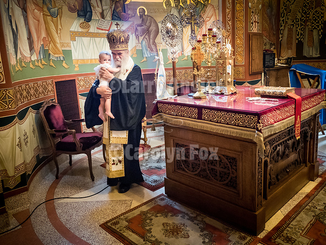 A baptist of an infant boy who is brought past the altar by Metropolitan Amphilohije inside the chapel at New Gračanica Monastery, Third Lake, Illinois.<br /> <br /> #NGMWADiocese<br /> #GlorificationStMardarije, #Chicago, #PatriarchIrinej, #MetropolitanAmphiloije<br /> #SerbianOrthodoxChurch
