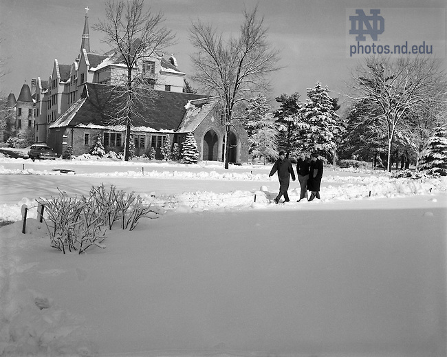 GPHR 45/1294:  Three male students walking across campus in winter with snow, December 1950.  In the background are the Knights of Columbus Council Hall, Walsh Hall, and the Basilica of the Sacred Heart steeple.  Image from the University of Notre Dame Archives.