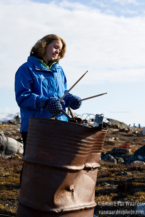 A young woman makes music with drumsticks on old military garbage in Northern Canada, Nunavut. The woman is part of the Cape Farewell Youth Expedition that was organized by the British Council of Canada. She is playing in an impromtu concert designed as part of a program to use art to communicate climate change.
