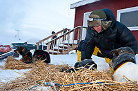 Veterinarian Heather Low examines a Ken Anderson dog book at the village checkpoint of Ruby in Interior Alaska during the 2010 Iditarod