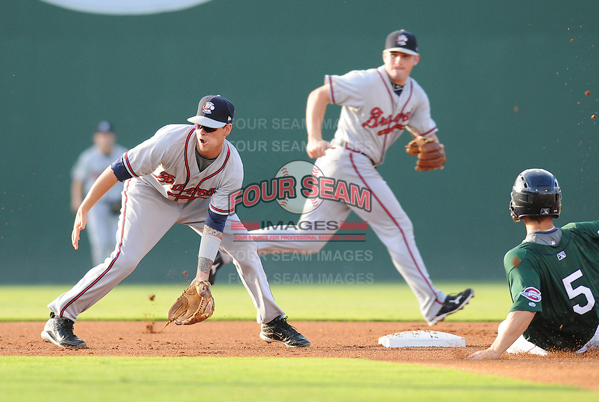 Infielder Matt Weaver (4) of the Rome Braves gets the ball too late to prevent a steal by Sean Coyle (5) of the Greenville Drive in a game on July 17, 2011, at Fluor Field at the West End in Greenville, South Carolina. (Tom Priddy/Four Seam Images)